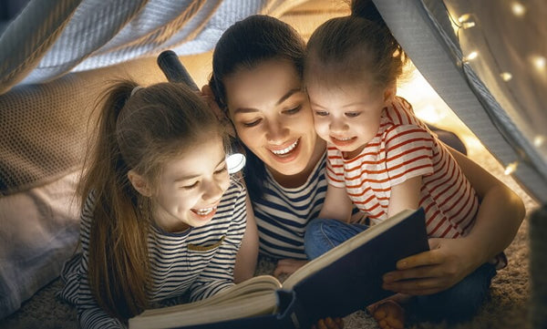 Mother and two kids reading Christmas books by torchlight