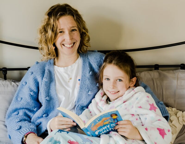 Mother and daughter together holding a book and reading a bedtime story