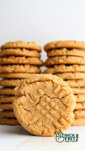 Vertical photo of two stacks of peanut butter cookies with one cookie facing the front against a white background