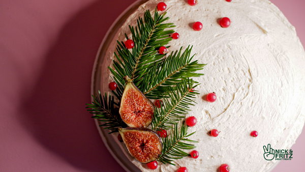 Overhead photo of a white frosted cake decorated with pine branches, fig, & red currents