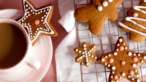 Overhead photo with a pink coffee cup on the left & gingerbread cookies on the right