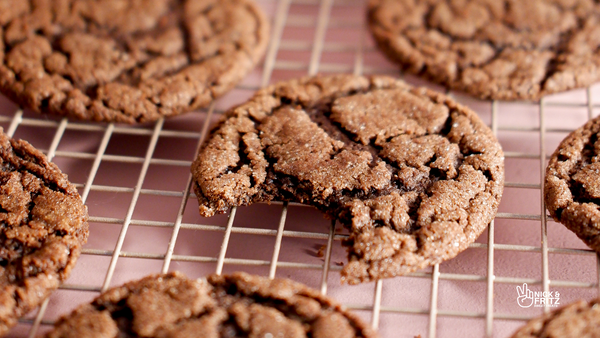 Horizontal photo of a chocolate cookie with a bite out of it on a cooling rack