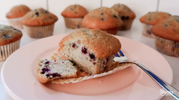Photo from the front of a half-eaten blueberry muffin on a pink plate with more muffins in the background