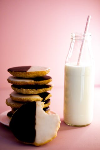 Vertical photo of a stack of Black-and-white cookies next to a glass bottle of milk
