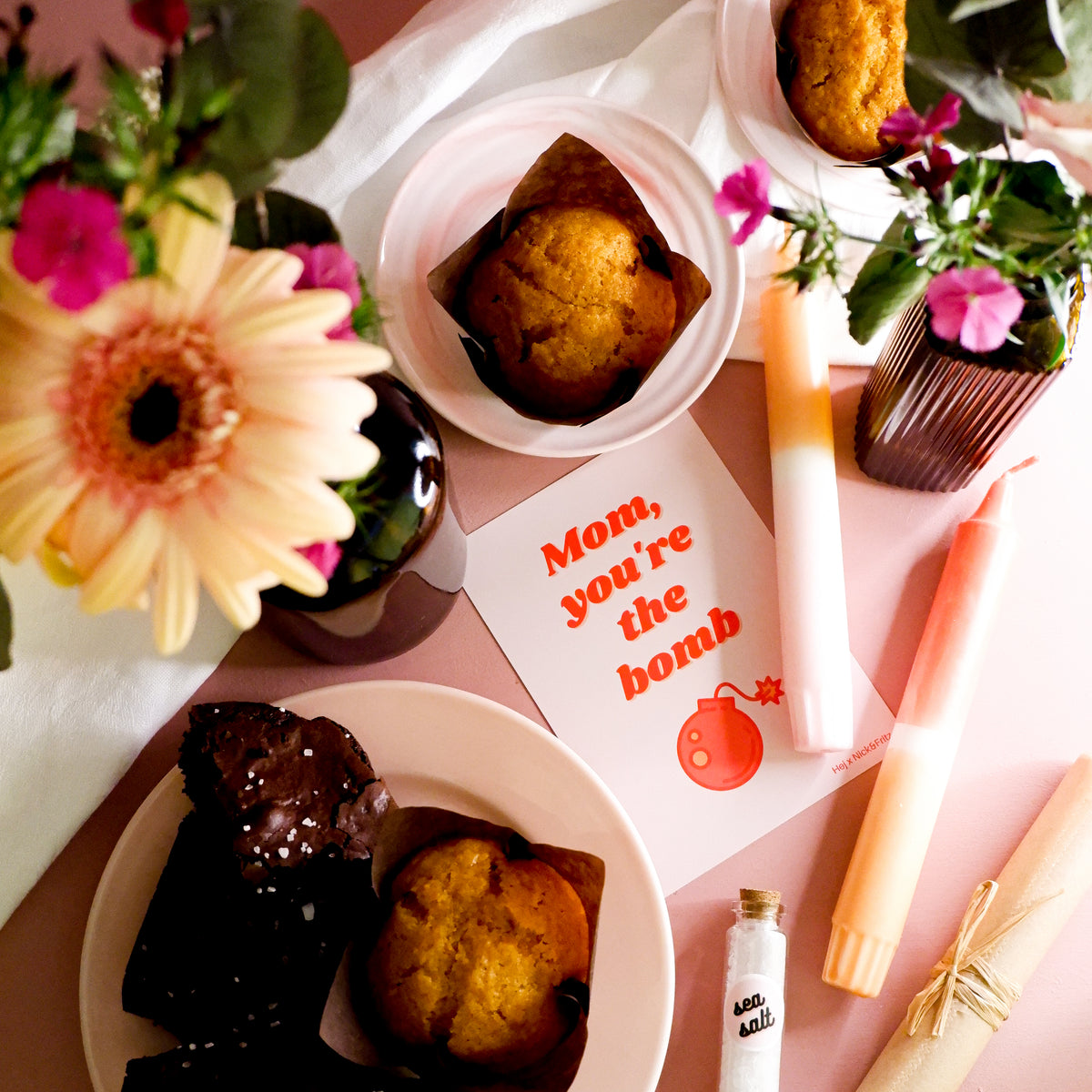 Overhead photo of a carrot muffin on a pink plate, 2 flower vases, 2 dip-dyed candles, and a mother's day card