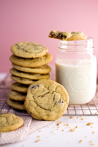 Photo of a stack of chocolate chip cookies on a cooling rack next to a mason jar filled with milk