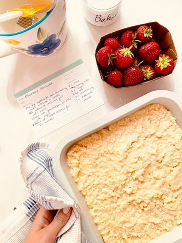 Overhead photo of a shortcake batter in a square pan with strawberries next to it