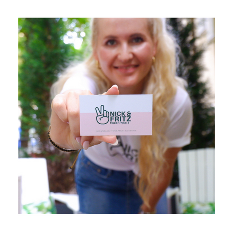 Square photo of Nick&Fritz Founder holding the business card: pink bottom half with the green logo