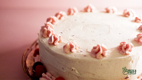 Photo of a layer cake decorated with 2 shades of pink frosting & fresh berries