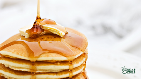 Photo of stack of pancakes with butter on top and maple syrup being poured over them