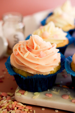 Close up photo of a cupcake with pink frosting & blue wrapper