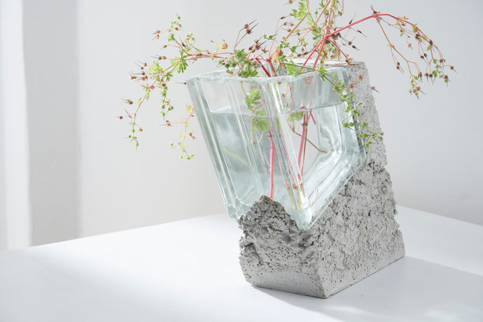 a vase made out of recycled glass brick and raw concrete set in white minimalistic interior on a table with decent flower.