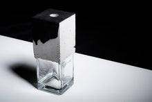 Load image into Gallery viewer, a vase made out of recycled glass and raw concrete set in black and white minimalistic interior on a white table with black background.