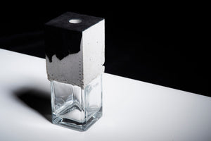a vase made out of recycled glass and raw concrete set in black and white minimalistic interior on a white table with black background.