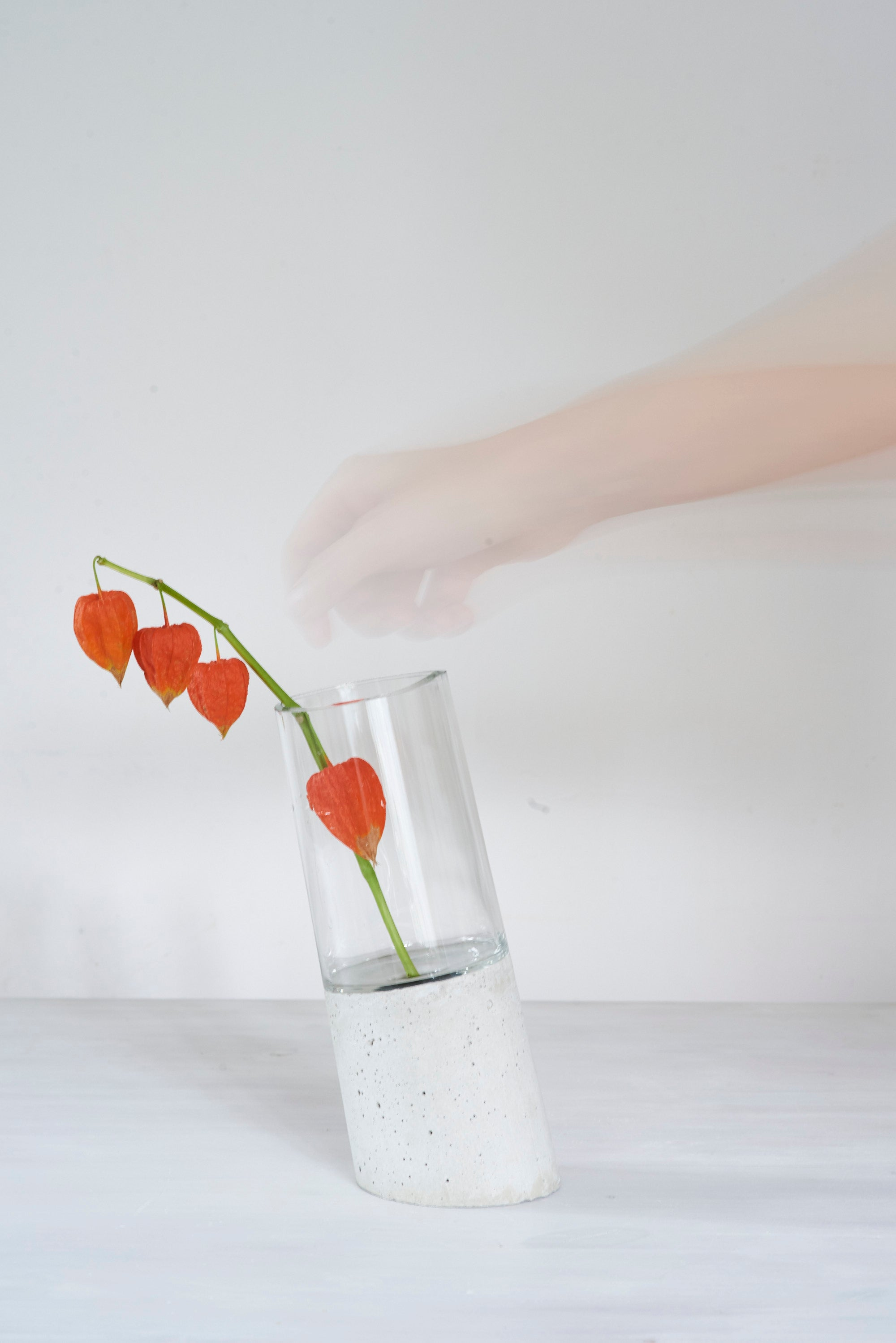 a vase made out of recycled glass and raw concrete set in white minimalistic interior on a table with decent flower.