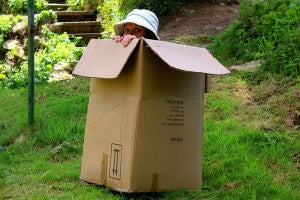 Move_house_woman_peeking_out_of_cardboard_box