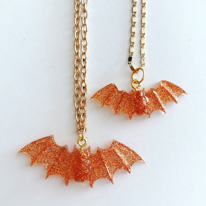 A set of orange glitter resin bats, the larger one on a gold necklace chain and the smaller one on a gold bracelet or anklet chain