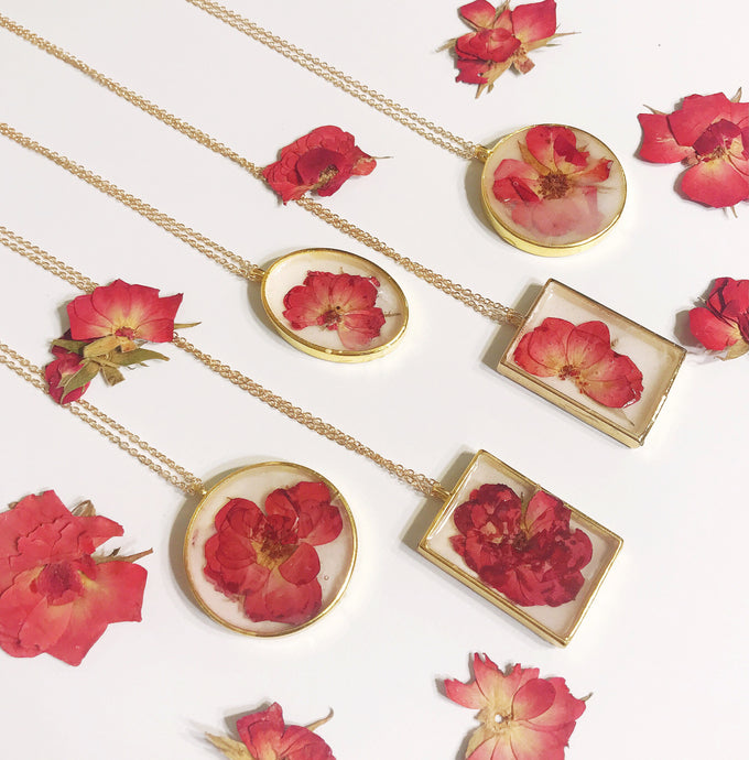 Five gold necklace pendants containing milky white resin with a red rose preserved inside