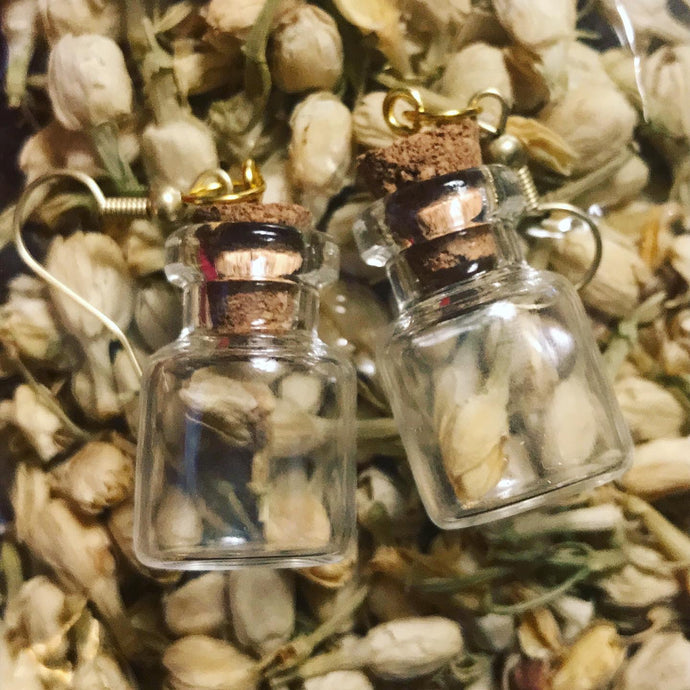 A pair of earrings made from two mini glass bottles each containing a single dried white rose, hanging from gold hooks