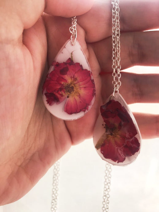 Two milky white resin pendants with preserved red roses inside, unframed and on silver chains