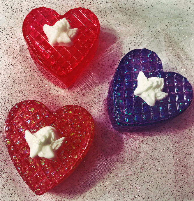 Three heart-shaped trinket boxes, all with white angels on top, the top box is red jelly appearance, the middle purple glitter, and the bottom is red glitter
