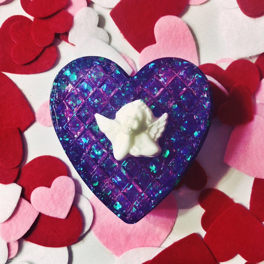 The purple glitter heart-shaped trinket box with a white angel on top, in front of a background of felt hearts