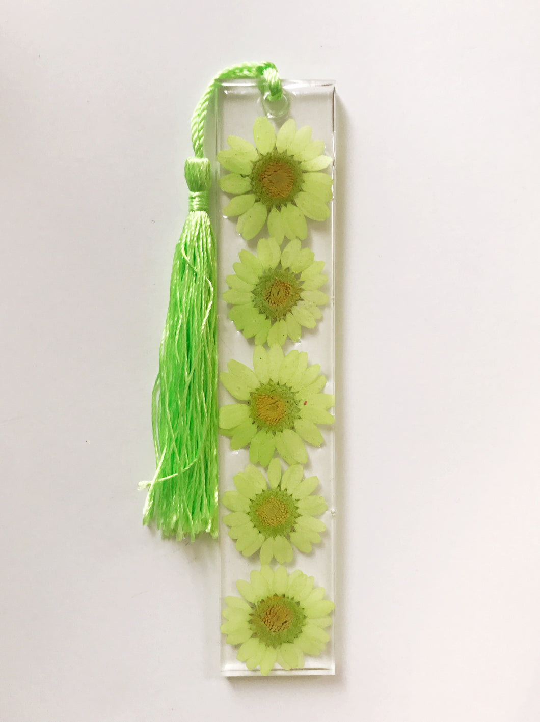 A resin bookmark with 5 lime green daisies inside with a matching lime green tassel