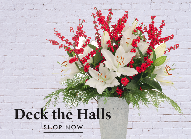 Deck the Halls Bouquet of Fresh White Lilies, Red Ilex and Holiday greenery. The perfect bouquet to celebrate the holidays.