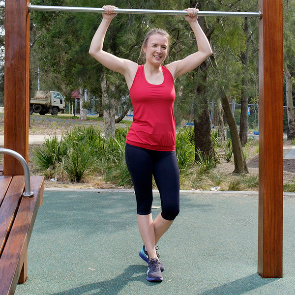 svvet real woman standing at park with arms on chin-up bar