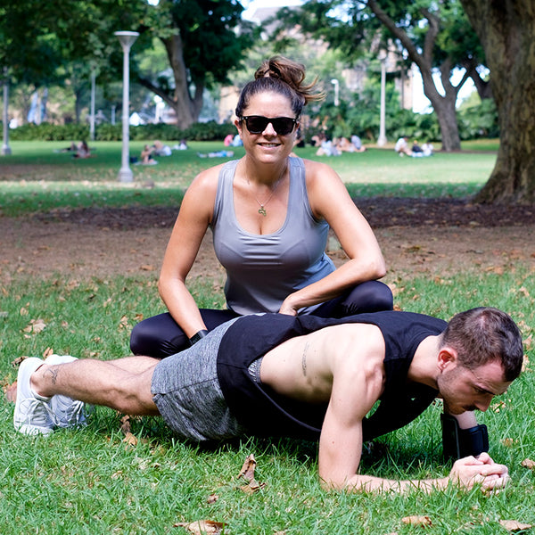 svvet real woman personal trainer next to client performing a plank hold in a park