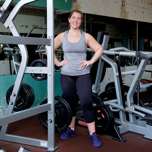 svvet real woman at a gym standing with hands on hips next to weightlifting equipment