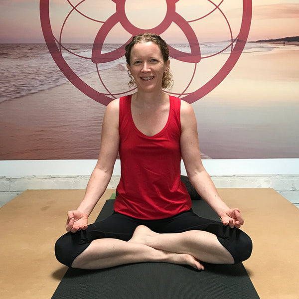 svvet real woman sitting cross-legged on a yoga mat