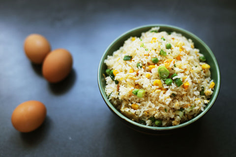 Bowl of egg fried rice next to three eggs