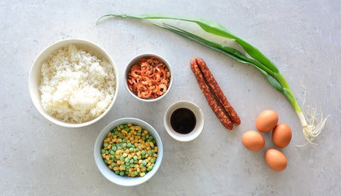 Ingredients for egg fried rice, eggs, spring onion, lap cheong, Chinese sausage, peas, sweetcorn, dried shrimp, rice, light soy sauce