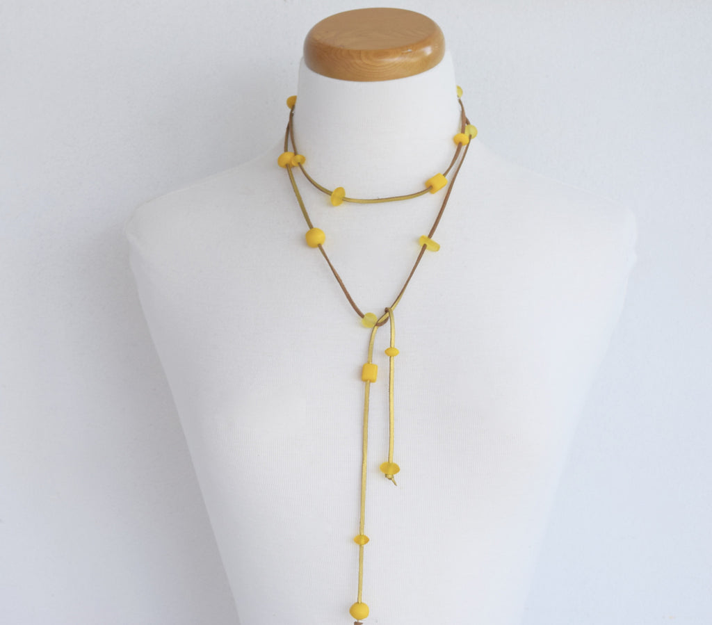 Resin bead lariat. Assortment of yellow resin beads on gold suede.