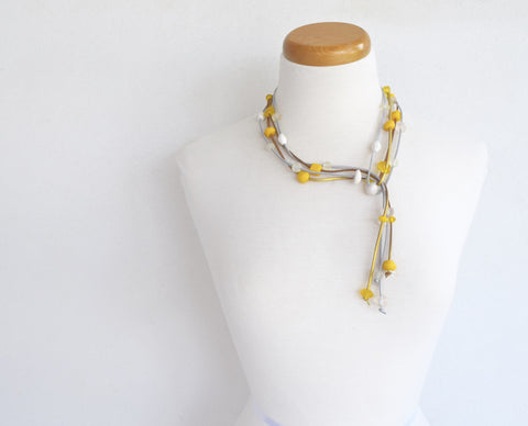 Resin bead double strand lariat. Assortment of yellow & white resin beads on gold suede.