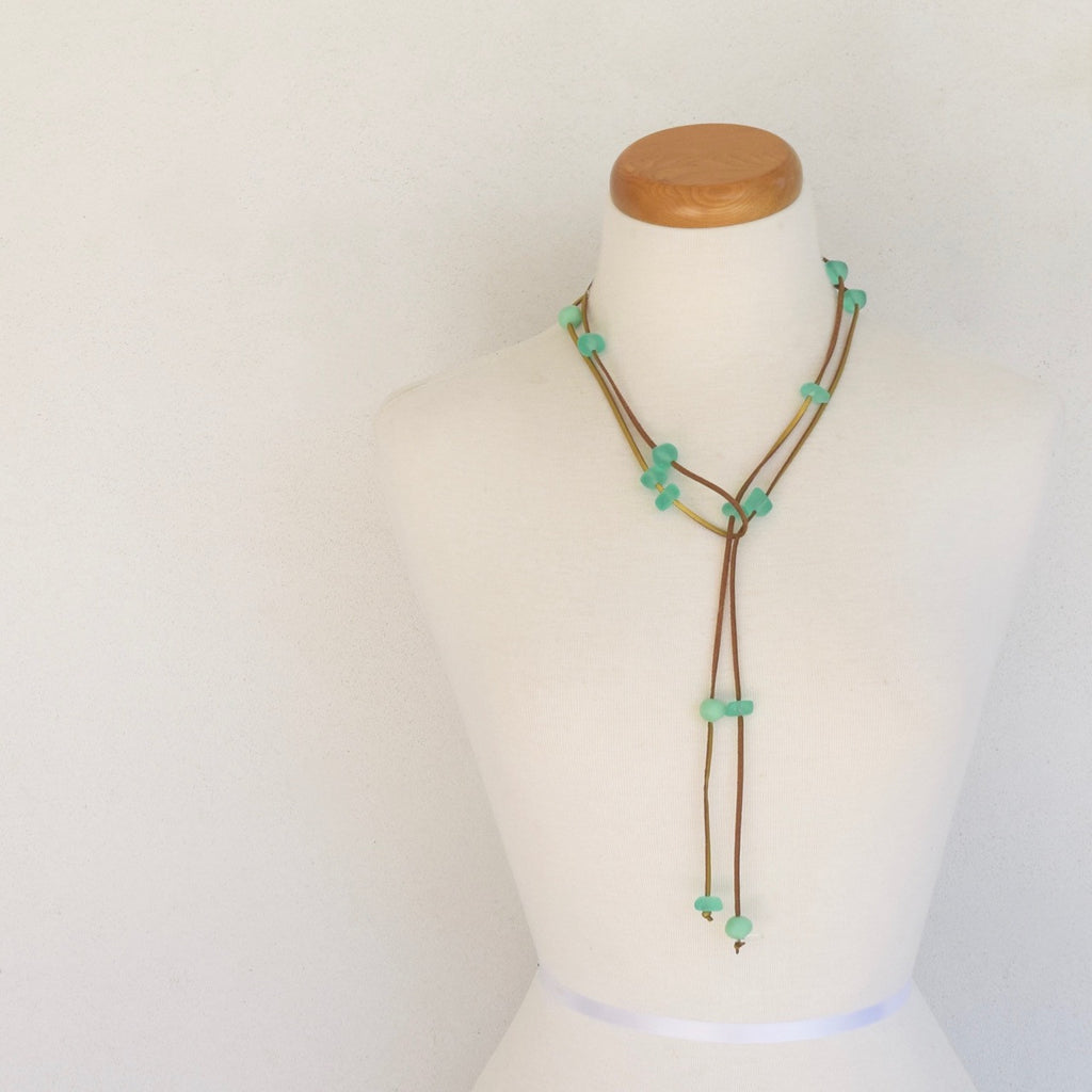 Resin bead lariat. Assortment of mint resin beads on gold suede.