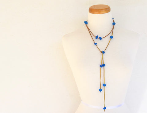 Resin bead lariat. Assortment of blue resin beads on gold suede.