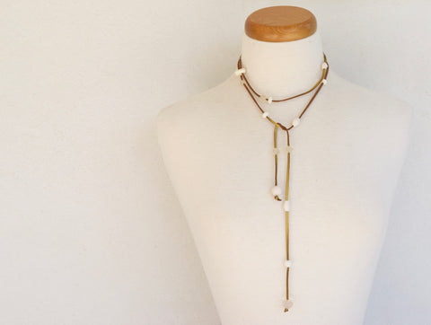 Resin bead lariat. Assortment of white resin beads on gold suede.