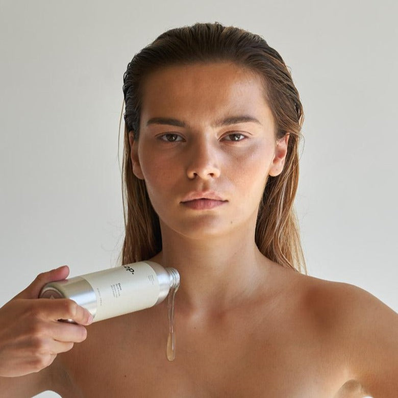 Woman using Sop Dene bodywash - Bergamot and Black Pepper
