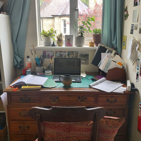 An old antique desk with draws, featuring a mug, laptop and some papers on it/
