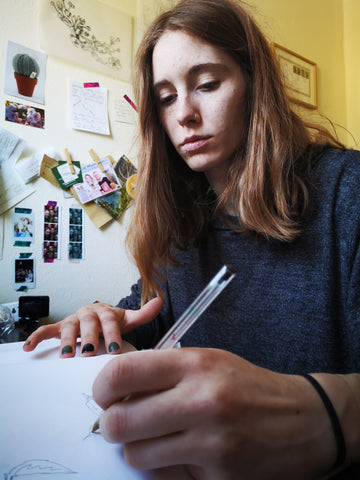 Kat drawing at her desk in her little studio, using a biro. The wall behind her is covered in postcards, lists and artwork.