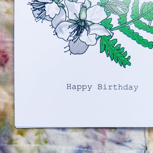 Close up of the bottom left of the card, featuring the words 'Happy Birthday' below the white blossom and green leaves. Behind the card is an abstrac naturally dyed piece of fabric featuring a variety of different tones of red, green, brown, purple and blue.