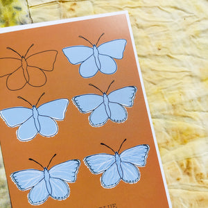 Close up of the Common Blue Butterfly. A warm orange portrait card with six butterflies in rows of two. The butterflies are in the different stages of drawing showing the illustration going from just an outline to the full piece. At the bottom of the card is the english and latin names of the butterfly. Behind the card are naturally dyed fabrics featuring warm yellow, blue and orange tones. - Duck Egg Designs Co