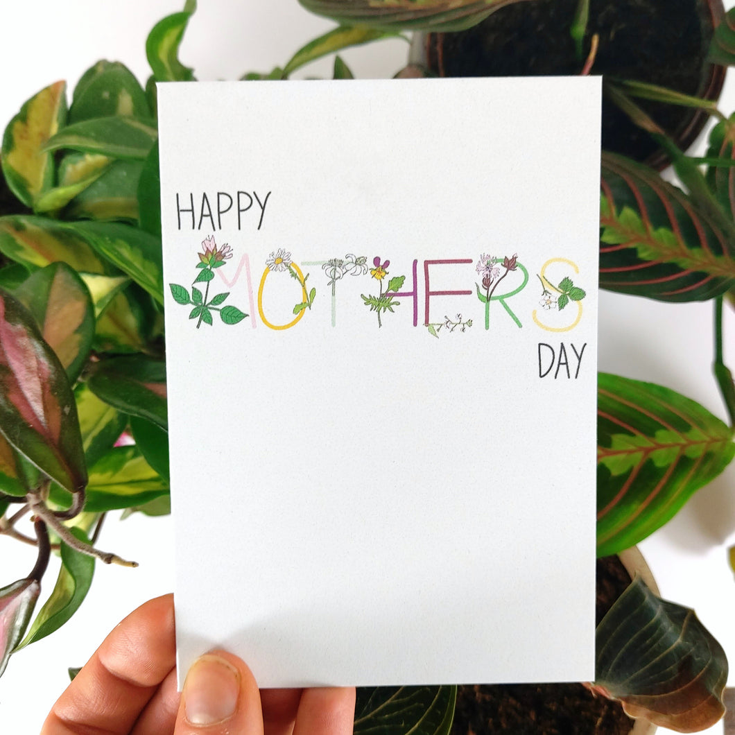 A white card held in front of some colourful houseplants (a hoya carnosa tricolor, a maranta leucona and a ludisia discolor) behind which are a white background. Across the card you can see the words HAPPY MOTHERS DAY the word mother is in colourful writing with the corresponding flowers on the letters.