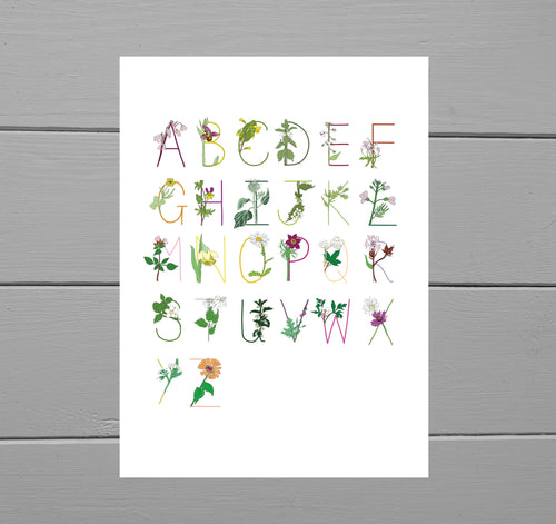 Full floral A to Z  print on a white base. Each letter is a different colour and has a corresponding flower. Behind the art print is a grey wooden plank background.