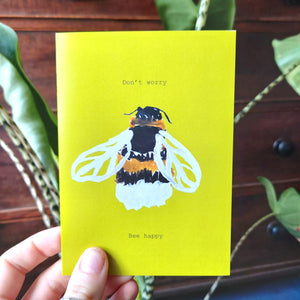Warm yellow card featuring a hand drawn bee and the words 'Don't worry Bee happy'. Behind the card is a stripy stemmed leafy houseplant, behind which is a mahogany chest of draws.