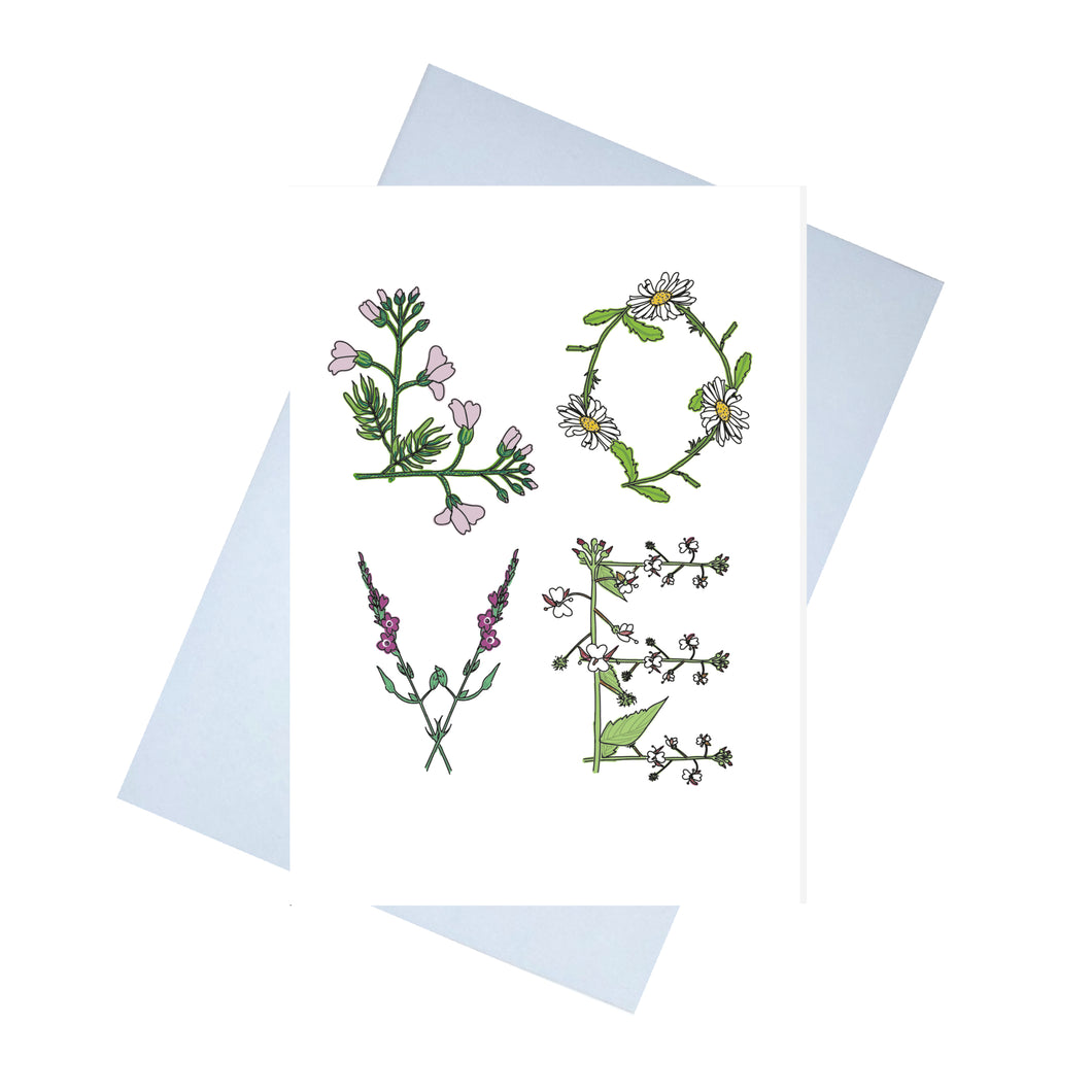 A white card with the word LOVE written on it in large. The letters are made up of flowers that begin with the same letter. L - lady's smock. O - ox-eye daisy, V - vervain and E - enchanters nightshade. Behind the card is a lilac envelope, behind which is a white background.