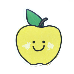 Granny smith green apple sticker, featuring a brown stalk and a green leaf. The apple has a simple smiley face and shaded cheek detailing for a cutelook. Behind the sticker is a white background.
