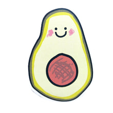 Load image into Gallery viewer, Smiley avocado sticker, featuring a smiley face and shaded cheeks, with a brown pit in the middle. Behind the sticker is a white background.